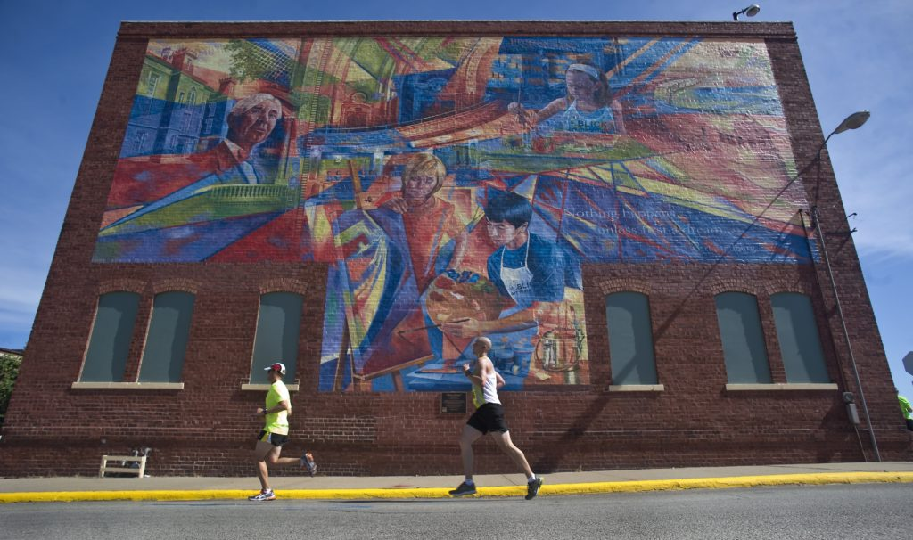 "Runners in Galesburg's half marathon, ""Run Galesburg Run,"" pass Discovery Depot Children's Museum as they head toward the finish line. Photo by Kent Kriegshauser."